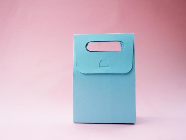 Синий пустой подарочный пакет на розовом фоне для вашего дизайна.
