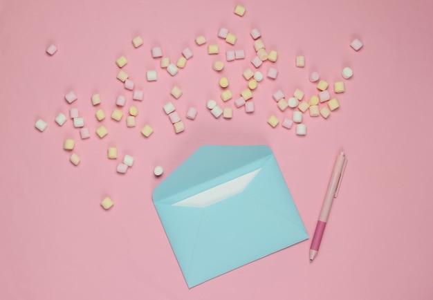 Синий конверт с ручкой и зефиром на розовом фоне. плоский макет на день святого валентина, свадьбу или день рождения. вид сверху
