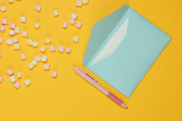 Синий конверт с ручкой и зефиром на желтом фоне. плоский макет на день святого валентина, свадьбу или день рождения. вид сверху