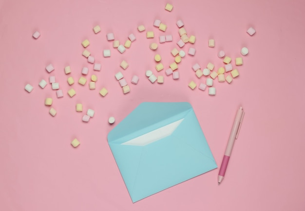 Blue envelope with pen and marshmallows on pink background. flat lay mockup for valentines day, wedding or birthday. top view