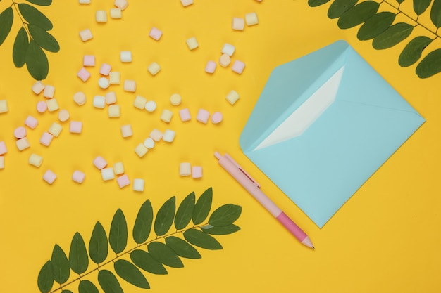 Blue envelope with pen and marshmallows on yellow background. flat lay mockup for valentines day, wedding or birthday. top view