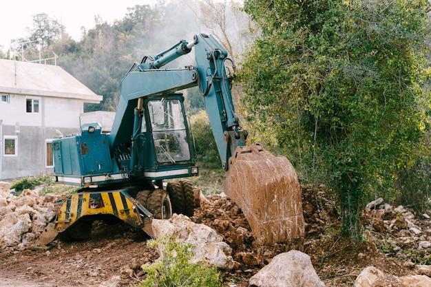 블루 굴삭기는 집과 녹지를 배경으로 건설 현장에서 작동합니다.