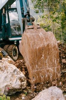 푸른 색 굴삭기는 녹지를 배경으로 건설 현장에서 작동합니다.