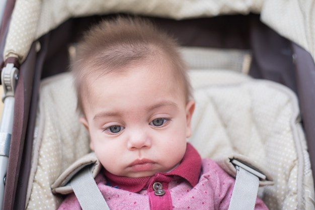 Blue-eyed baby boy in baby stroller