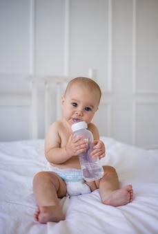 Голубоглазая девочка в подгузнике пьет бутылку воды на белом хлопковом одеяле на кровати в комнате