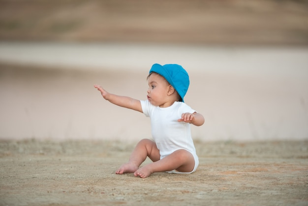 Blue-eyed baby with blue hat sitting on the sand floor