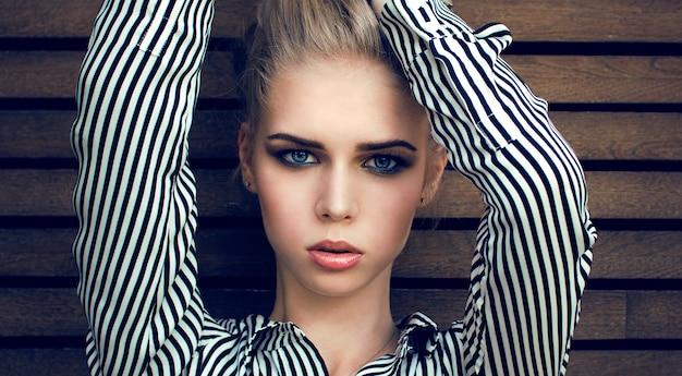 Голубоглазая блондинка в полосатой рубашке позирует
