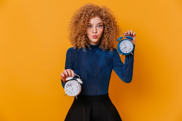 Blue-eyed curly blonde lady in striped sweater and skirt whistles and poses with alarm clocks on yellow space.