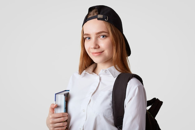 Blue eyed delighted schoolgirl holds book, carries backpack, wears black cap, going to library, reads and cramms material for exam, poses on white. studying and school concept