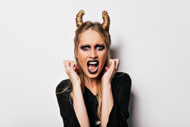 不愉快な表情で魔女の衣装でポーズをとる青い目のヨーロッパの女性。黒の化粧で怒っている金髪の吸血鬼。