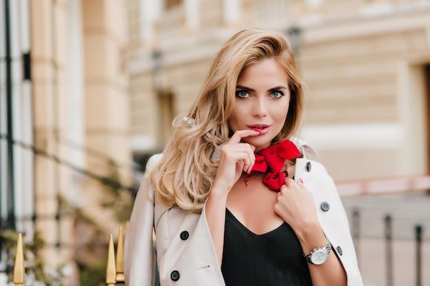 Modello femminile dagli occhi azzurri in sciarpa rossa alla moda in posa con piacere in abito nuovo in piedi accanto all'edificio