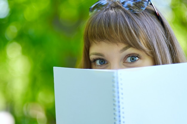 Blue eyed female student is hiding behind a book. student hiding behind book