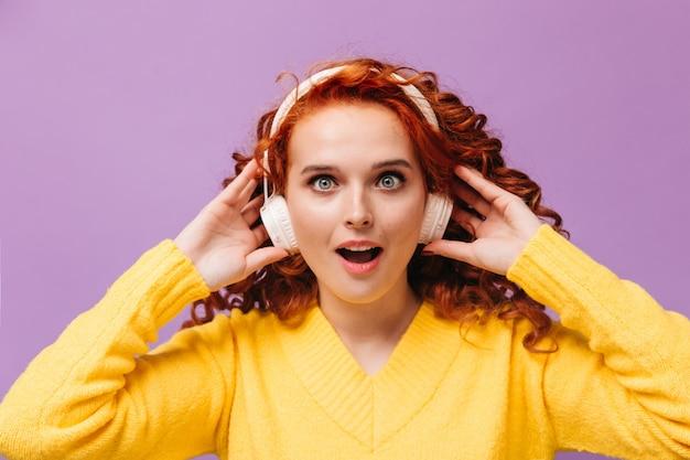 笑顔で黄色いセーターを着た青い目の女の子が紫色の壁に向かってヘッドフォンで音楽を聴いています