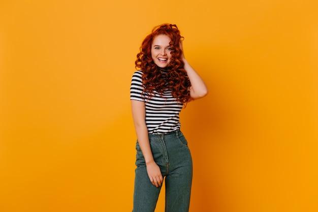 笑顔でカメラを見ている赤い巻き毛の青い目の女の子。デニムパンツと白黒tシャツの若い女性の肖像画。