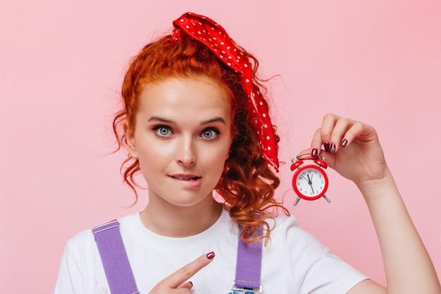Голубоглазая девушка с красной лентой в волосах прикусывает губу и указывает на будильник