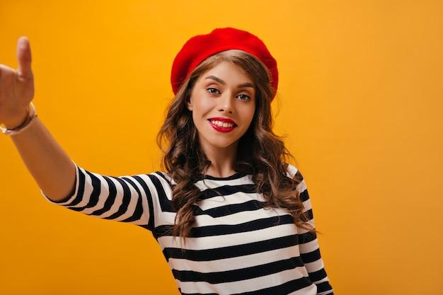 La signora dagli occhi blu in berretto rosso prende selfie su sfondo arancione. donna graziosa riccia in camicetta a righe in posa su sfondo isolato.