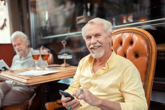 Голубоглазый мужчина. голубоглазый пенсионер держит смартфон, проводя время с другом