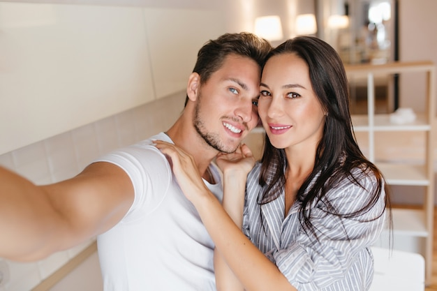 Blue-eyed man in white t-shirt making selfie with lovely black-haired woman in home