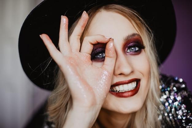 좋은 감정을 표현하는 파란 눈의 긍정적 인 소녀. 모자에 평온한 백인 여자의 실내 샷.