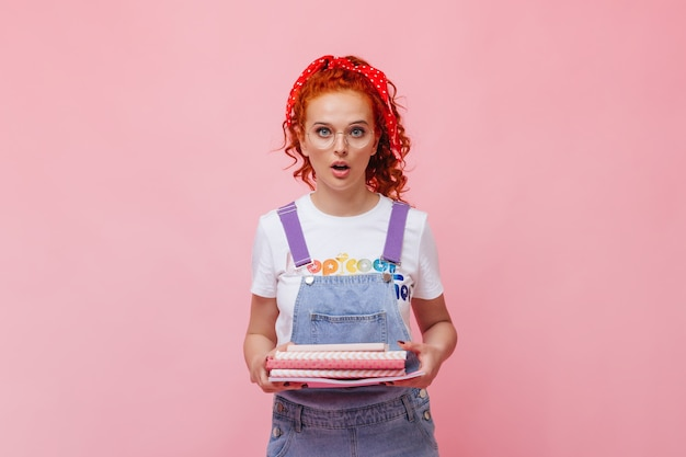 Blue-eyed red-haired girl in jeans outfit and glasses looks at front and holds pink books on isolated wall