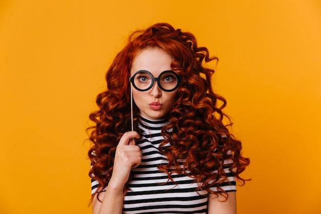 스트라이프 티셔츠에 파란 눈의 빨간 머리 여자는 키스를 불면 오렌지 공간에 대해 포즈를 취하는 스틱에 장난감 안경을 보유하고 있습니다.