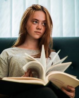 Blue eyed redhead girl with serious facial expression sitting on a couch in public library and browsing through a book while looking away.