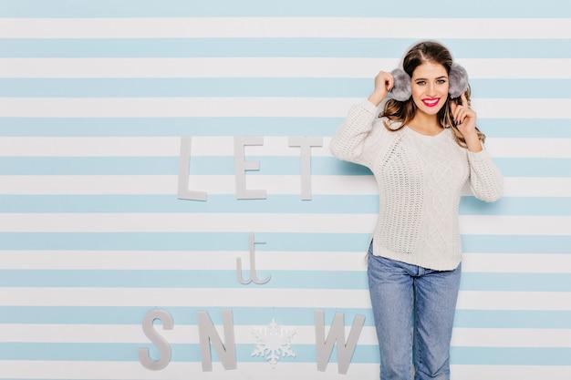 明るい唇を持つ青い目の笑顔の女の子は、壁のテキストに対してポーズをとります。暖かい冬の服装のフルレングスの肖像画