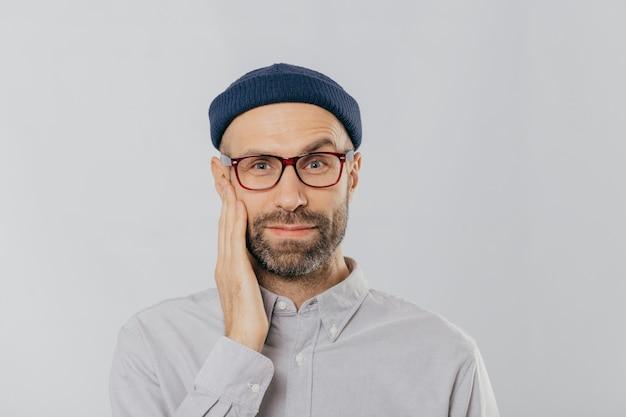 Blue eyed unshaven man raises eyebrow, keeps hand on cheek, looks happily, wears eyewear, dressed in black hat and shirt