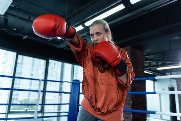 青い目の女性。ボクシングのリングの真ん中に積極的に立っている灰色のレギンスボクシングを身に着けている青い目の女性