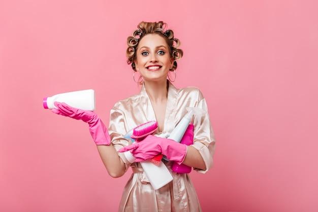 正面を見て洗剤を持って笑顔でヘアカーラーの青い目の女性
