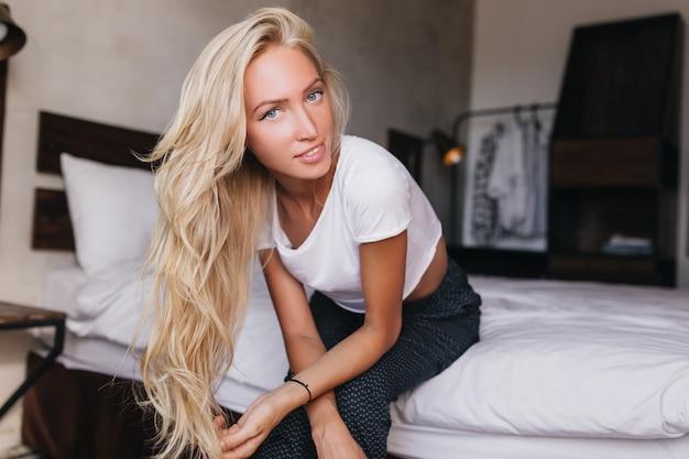 興味のある表情でベッドに座っている金髪のウェーブのかかった髪の青い目の女性。週末に彼女のアパートで身も凍るようなパジャマ姿の白人女性。
