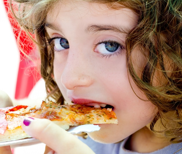 Blue eyes child girl eating pizza slice