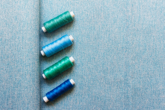 Blue fabric cloth textile with four green blue sewing threads