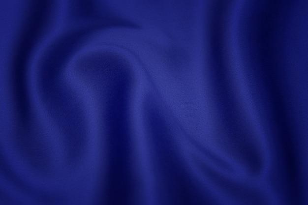 青い布のテクスチャ背景、波状の布の柔らかい青い色、豪華なサテンまたはシルクの布のテクスチャ。