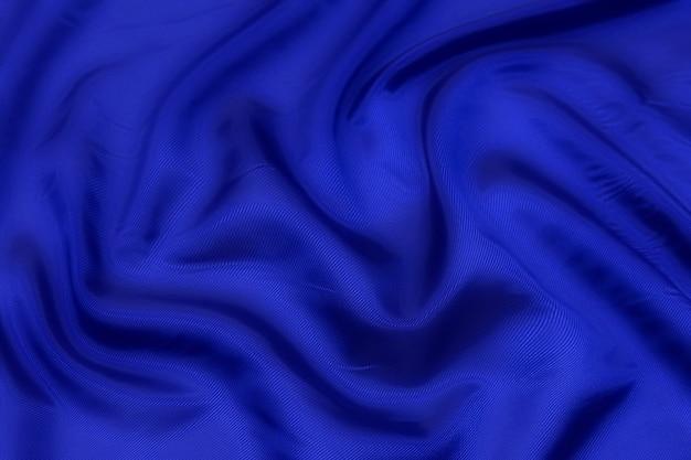 青い布のテクスチャの背景、波状の布の柔らかい青い色、豪華なサテンまたはシルクの布のテクスチャ。