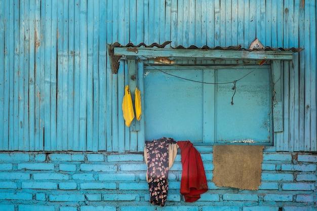 Facciata blu di un vecchio edificio suburbano in legno con vestiti appesi alla finestra