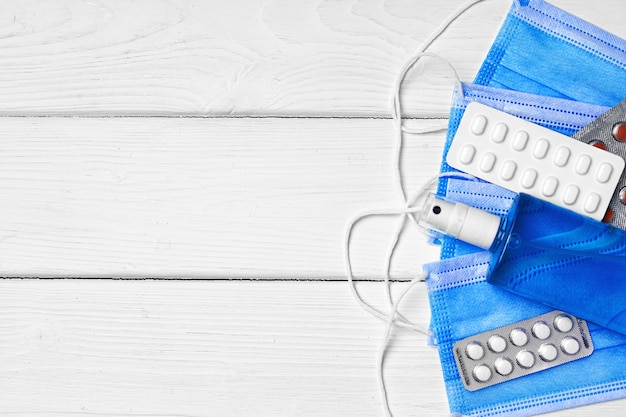 青いフェイスマスク、錠剤、木製の消毒ジェル