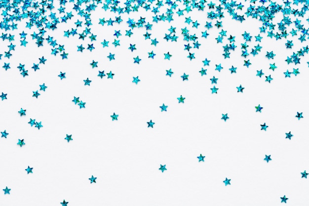 Blue falling stars glitter confetti on white festive background