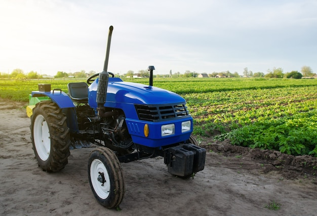 Blue farm tractor stands on field application of agricultural machinery in harvesting