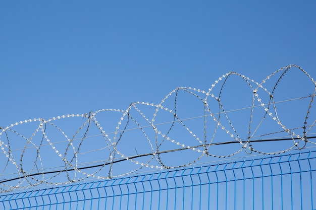 Blue fence with barbed wire on blue sky background. dangerous area.