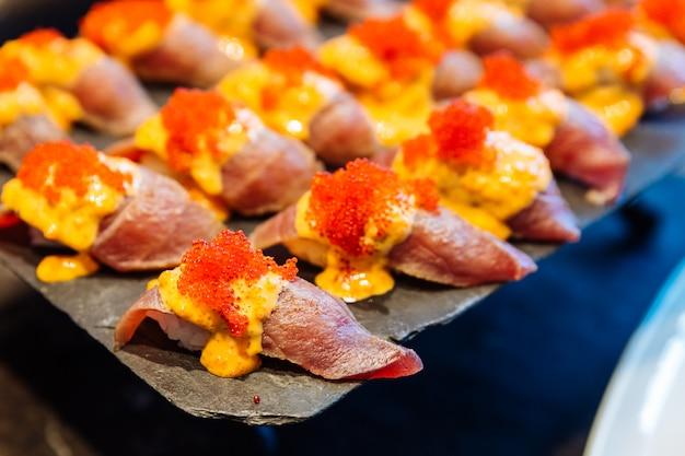 Blue fin tuna sushi topping with ebiko sauce and ebiko in buffet line.