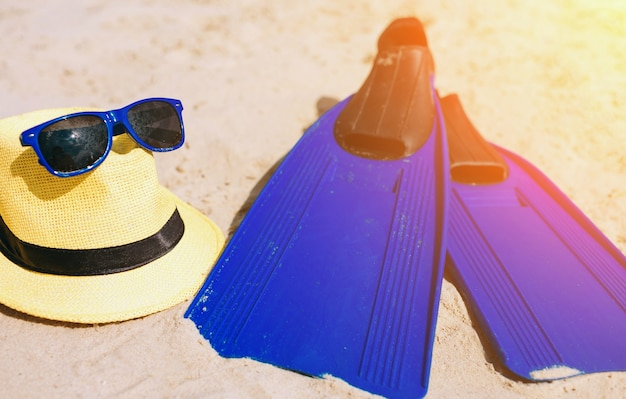 Blue fins hat and sunglasses on the sandy beach. bright outside. sun shines