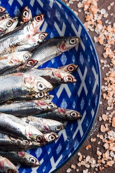 Blue fish. anchovies in a dish with pink salt