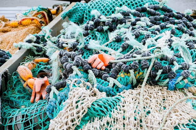 朝の霜で覆われたロープとフロートを備えたポンツーンの青い漁網