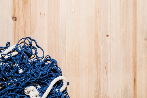 Blue fishing net on wooden backdrop