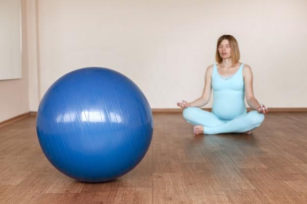 妊娠中の女性を背景に青いフィットネスボール。青く