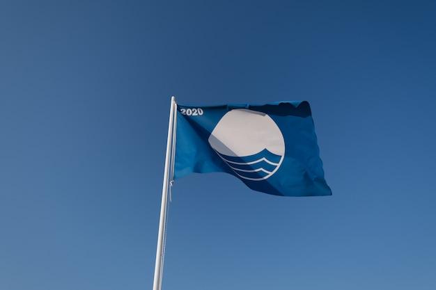 Blue flag beach 2020 on blue sky