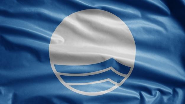 Голубой флаг развевается на ветру, международная награда для пляжей и пристаней для яхт. символ экологических пляжей на берегу моря