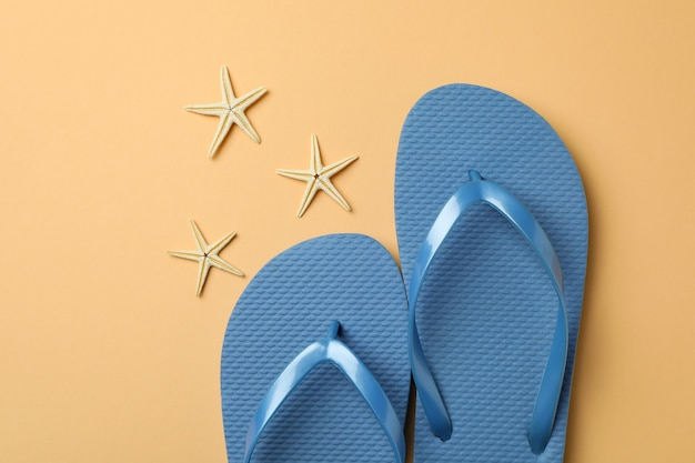 Blue flip flops and starfishes on beige isolated background