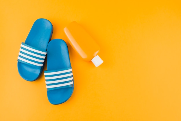 Blue flip-flops with sunscreen lotion bottle on yellow backdrop